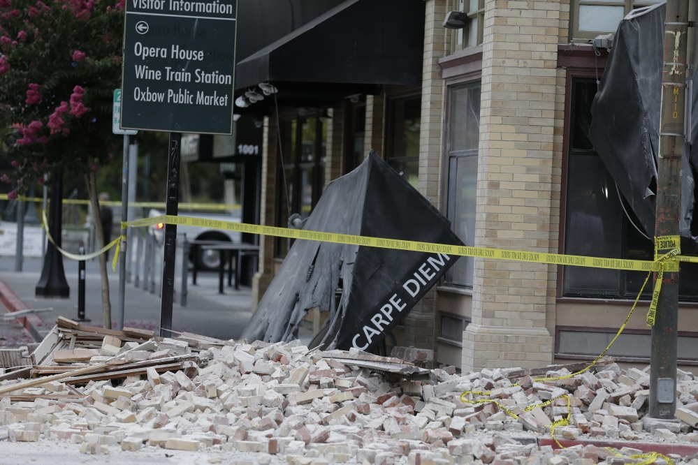 Bricks and rubble cover the sidewalk in front of a heavily damaged building following an earthquake on Sunday in Napa, Calif.