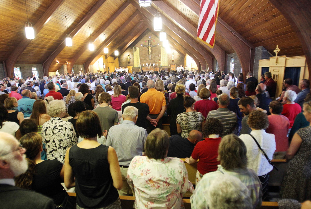 Mourners pack Our Lady of the Holy Rosary Catholic church during a special Mass for slain journalist James Foley in his hometown of Rochester, N.H., on Sunday. Bishop Peter Libasci implored those gathered not to hate but to heal.