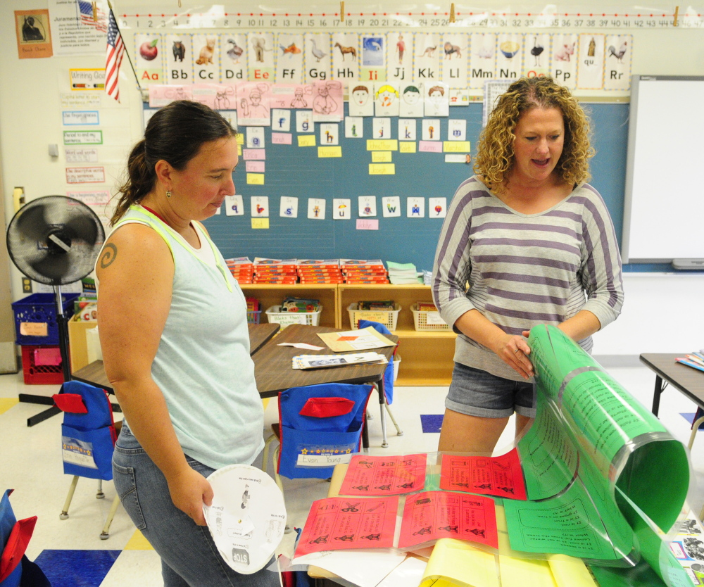 First grade teachers Shannon Morgan, left, and Jessica DeJongh look at the riddles Morgan had printed out for her students as they ready their classrooms at Farrington Elementary in Augusta for the new school year on Friday