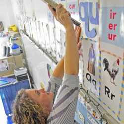 First grade teacher Jessica DeJongh staples letters to the word wall as she gets her classroom at Farrington Elementary in Augusta ready for the 2014-15 school year in this file photo.
