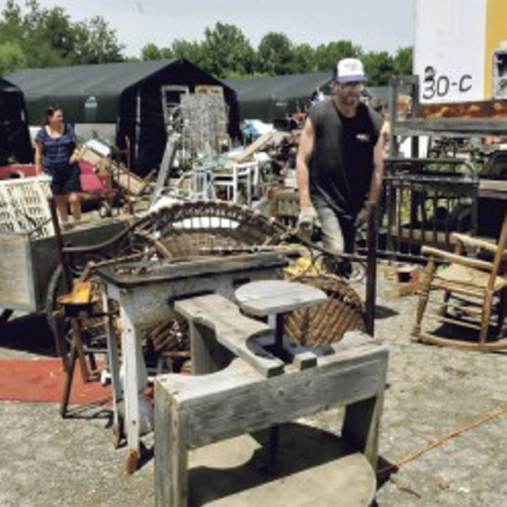 Robert Dale, owner of Maine 201 Antiques in Fairfield, walks around piles of scattered merchandise at his Fairfield property in June.