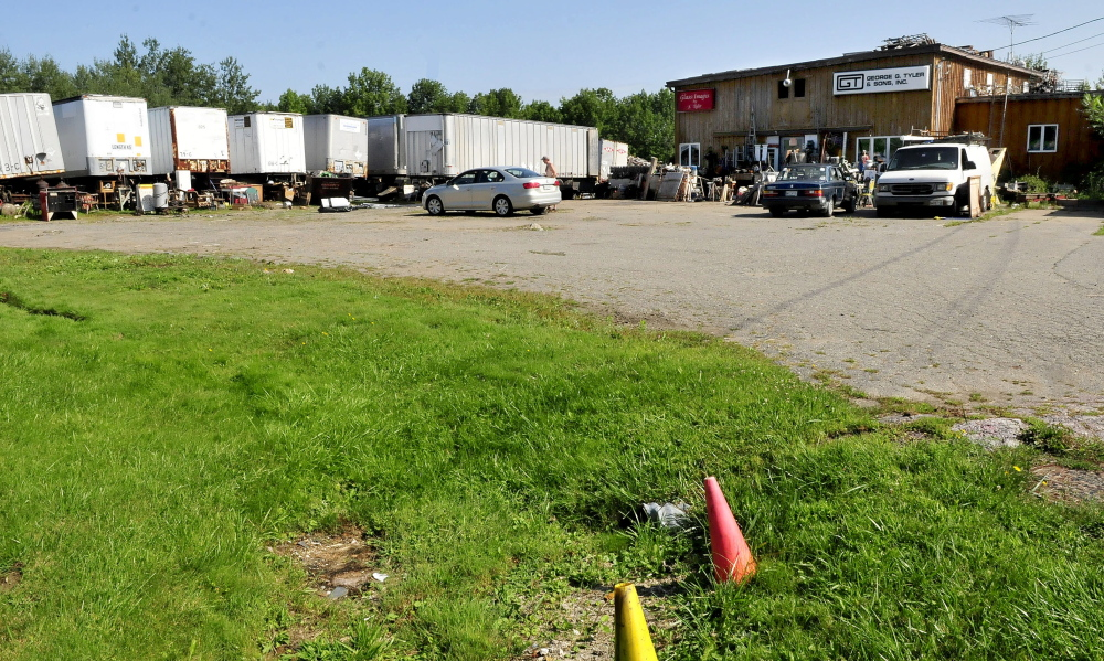 A man steps out of a car at the Maine 201 Antiques business in Fairfield on Sunday. The area in foreground was recently filled with used household and building materials which have been consolidated inside and behind trailers in background.