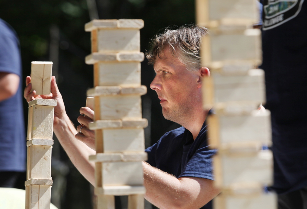 "Andy Baker, of West Hartford, Connecticut, participates in a block stacking challenge Sunday as part of the 2nd annual Durham Warriors Survival Challenge in Durham. The fundraiser is put on by ""Survivor"" winner Bob Crowley."
