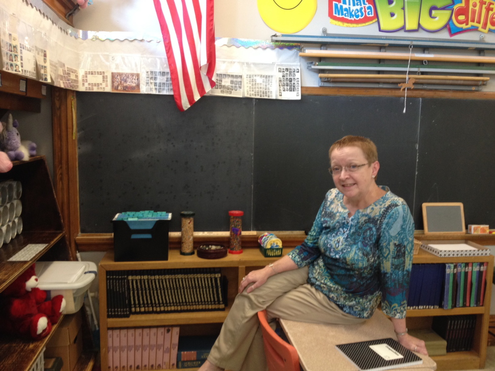 Laura Bushey sits below class photos from her first years of teaching. Bushey, who says the first day of school is her favorite day of the year, lines her classroom with class photos from her 39 years teaching.