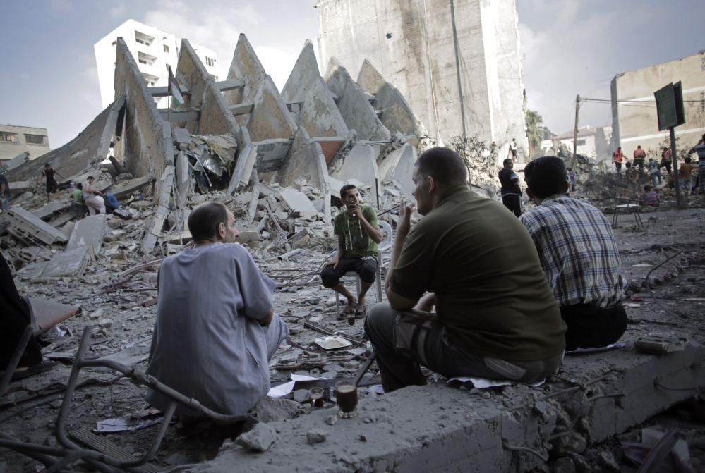 Palestinians have a coffee next to the rubble of the 15-story Basha Tower that collapsed from early morning Israeli airstrikes in Gaza City, Tuesday.