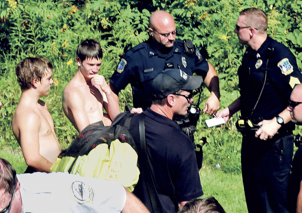 Police and rescue personnel speak with Aerrin Landry, 15, of Clinton, left, and Parish Napoleone, 14, of Winslow, who saw a woman jump from the Two-Cent Bridge into the Kennebec River and who jumped into the river and tried unsuccessfully to rescue her.