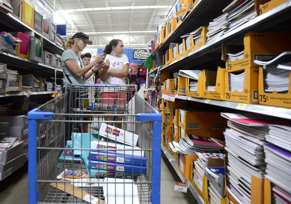 Karen Morgan, of Cumberland, checking her list, and children Mac Lindsay, 12, and Sabie Lindsay, 13, shop for school supplies Aug. 20 at Walmart in Scarborough.