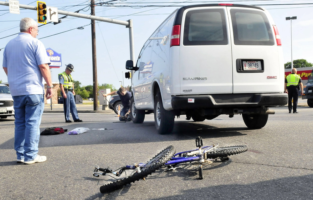 Donald Paradis watches as police reconstruct the scene of an accident after his van and bicyclist Mathew Grover collided on Upper Main Street in Waterville. Grover was seriously injured and flown via helicopter to the hospital.