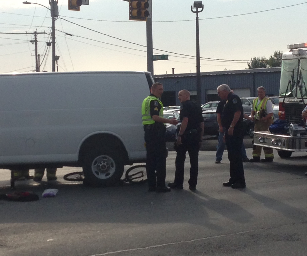 Staff photo by Jesse Scardina A bicyclist was pinned underneath a GMC van after being stuck by the front of the van at the intersection of Main Street and Armory Drive in Waterville Wednesday morning.