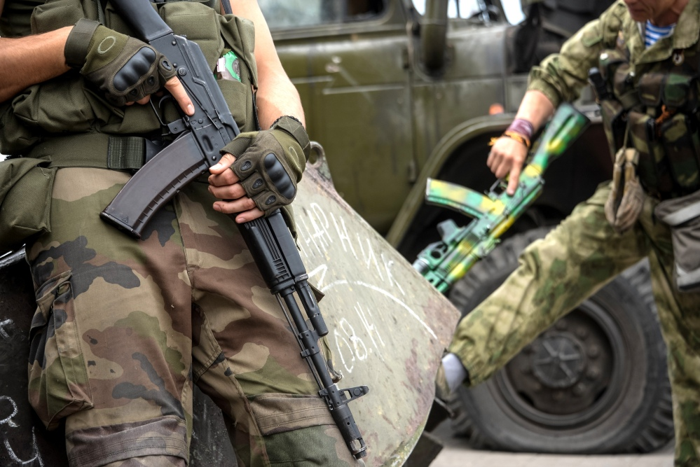 """Pro-Russian rebels hold their guns as they patrol the Lenin square in the town of Donetsk, in eastern Ukraine, on Thursday. Ukraine's President Petro Poroshenko called an emergency meeting of the nation's security council and canceled a foreign trip Thursday, declaring that """"Russian forces have entered Ukraine."""""""