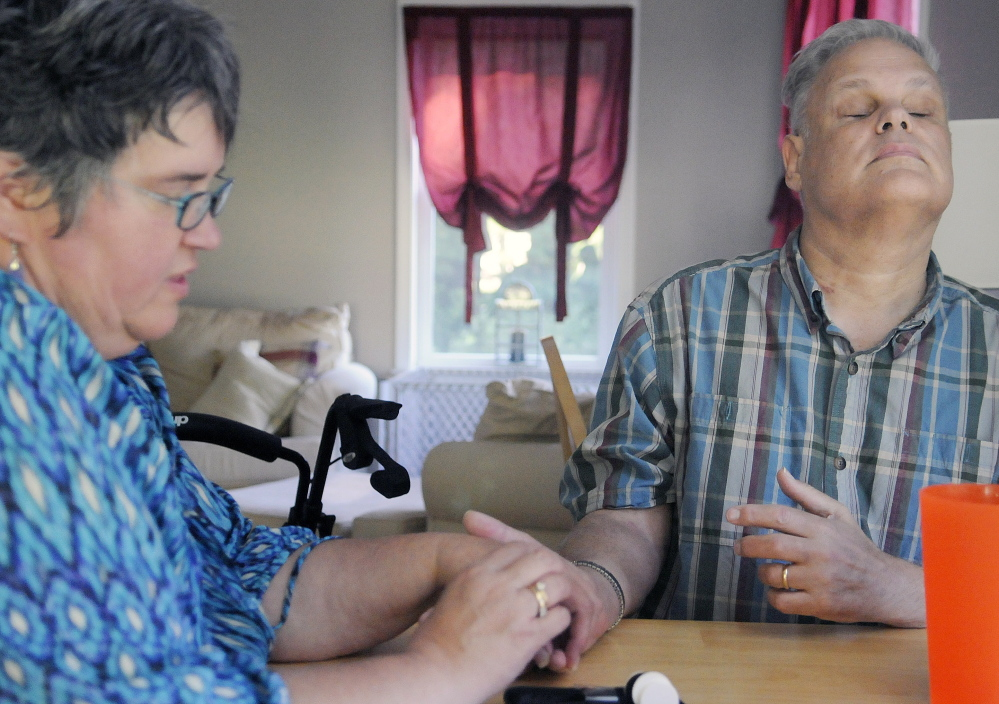 Julie Shephard checks the blood sugar level of her husband, Neal, on Thursday at their Farmingdale home. A musician, Neal Shephard is recovering from two strokes and hopes to learn how to play music again.