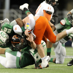 In this Dec. 2013 photo, Aledo quarterback Luke Bishop (4) is tackled by Brenham's Ryan Nunn (22) in the first half during the UIL Class 4A, Division II high school football championship game in Arlington, Texas. Nearly half of parents say they're not comfortable letting their child play football amid growing uncertainty about the long-term impact of concussions, according to an Associated Press-GfK poll. A majority, however, say they haven't prevented their child from playing the game they love.