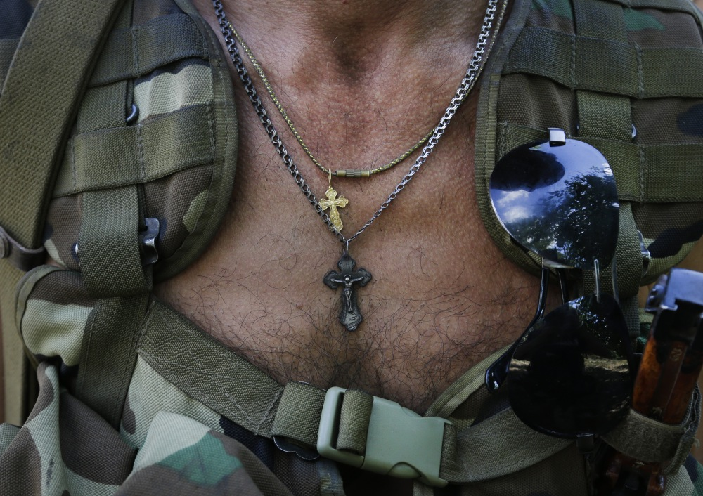 An Orthodox church crosses hangs on a chest of a pro-Russian rebel in the town of Novoazovsk, in eastern Ukraine, on Friday. In Novoazovsk, pro Russian rebel fighters looked to be in firm control, well-equipped and relaxed.