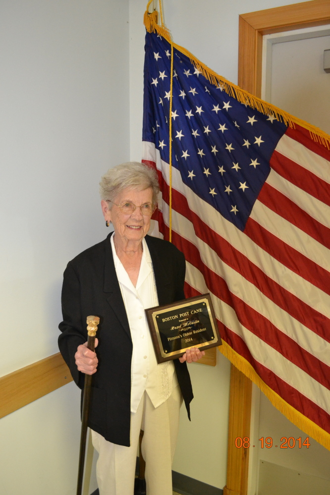 Hazel McCaslin holds Pittston's Boston Post Cane and a commemorative plaque she received.