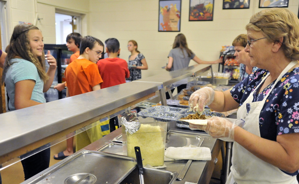 Layna LaBranche, right, serves tacos to students Friday during lunch period at Waterville Junior High School.