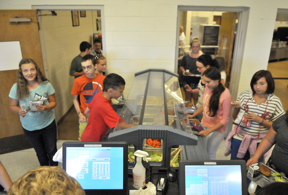 Students help themselves at the salad bar during lunch period Friday at Waterville Junior High School.