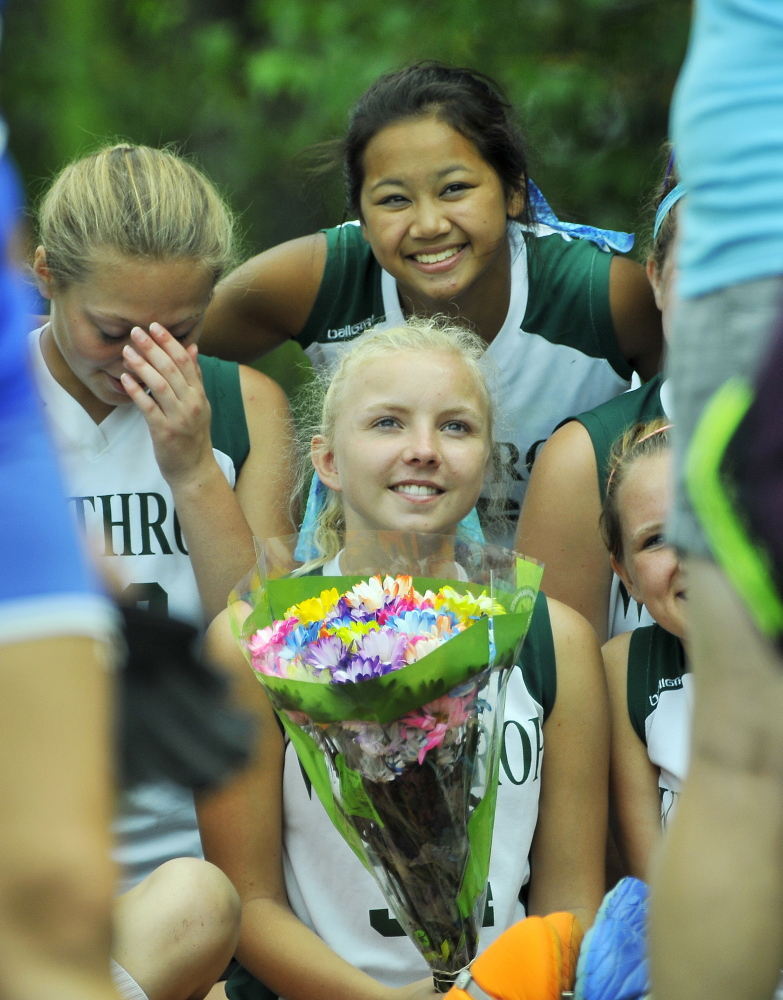 Winthrop High School's Maddy Thomas, center, smiles with teammates after receiving flowers from Messalonskee High School in memory of fallen teammate Kelsey Stoneton during Play Day hosted by Winslow High School in Winslow on Saturday.