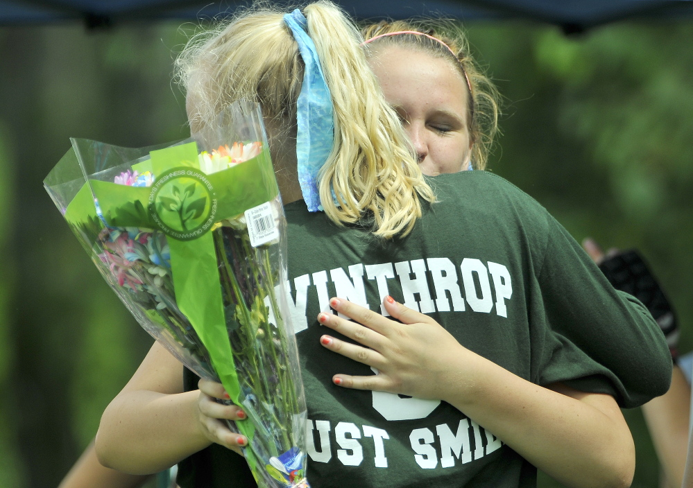 Maddy Thomas, foreground, is embraced by a teammate after receiving flowers from Messalonskee High School in memory of fallen teammate Kelsey Stoneton during Play Day hosted by Winslow High School in Winslow on Saturday.