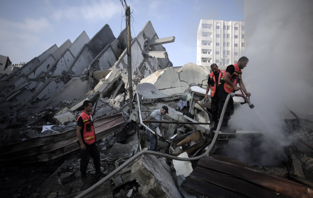 In this Aug. 26, file photo, Palestinian firefighters extinguish a fire in the rubble of the destroyed 15-story Basha Tower, following early morning Israeli airstrikes in Gaza City.