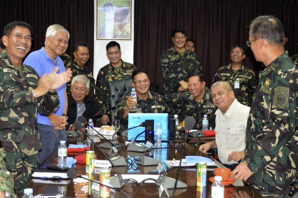 In this photo released by the Armed Forces of the Philippines Public Affairs Office, Philippine Military Chief Gen. Gregorio Catapang, center, reacts after learning about the safe repositioning of Filipino peacekeepers in Golan Heights as they monitor the situation with Philippine Foreign Affairs Secretary Albert Del Rosario, second left, Philippine National Defense Secretary Voltaire Gazmin, third from left seated, at Camp Aguinaldo military headquarters in suburban Quezon city, Philippines on Saturday.