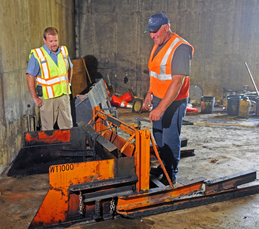 Augusta Public Works employees Jerry Dostie, left, and Mike Morrison talk about the WT1,000 during an interview Wednesday in Augusta. Morrison invented the machine, which is pushed by a skid steer and levels paving being put into the wheel tracks on a road.