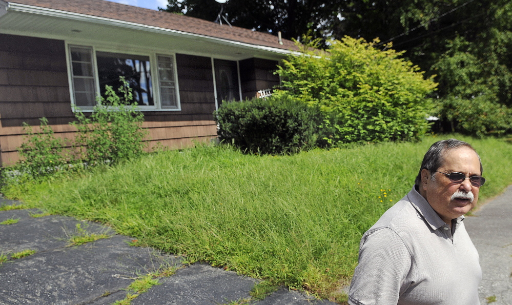 Keith Ludden stands on Thursday in front of a house on Brooklawn Avenue in Augusta that was lost to foreclosure. Ludden, who lives on the same street, said the house has been abandoned since November, and failure to maintain it might degrade the value of neighboring homes.