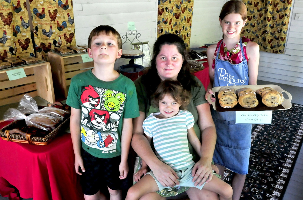 Jenny McLean sits with some of her children who help at the McLean Family Farm and Bakery in Winslow.