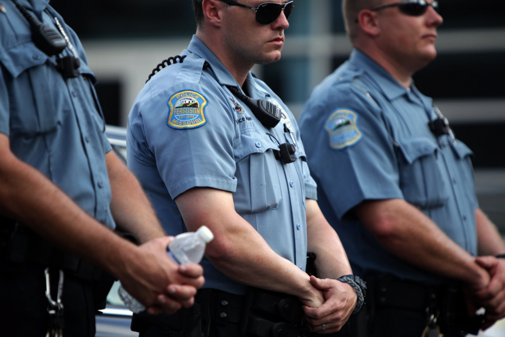 Police officers wear what appear to be body cameras as they hold the line against protesters gathered at the police station during a rally in Ferguson, Mo. on Saturday for Michael Brown, an unarmed black 18-year-old who was fatally shot by a white police officer three weeks earlier.