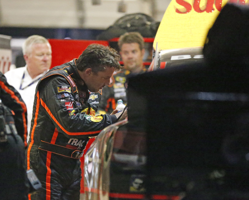 Tony Stewart looks over the damage to his car after he hit the wall during a NASCAR Sprint Cup race Sunday night at Atlanta Motor Speedway Sunday in Hampton, Ga. It was Stewart's first race back after his sprint car struck and killed Kevin Ward Jr. at a New York dirt track on Aug. 9.