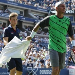 Lleyton Hewitt, of Australia, hands a towel back to a ball person after wiping sweat from his face and arms during the second round of the 2014 U.S. Open tennis tournament against.