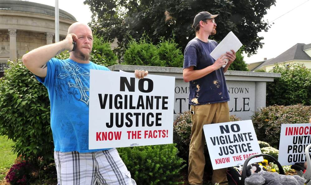 Joe Levesque, left, and James Hawkins hold signs Tuesday in Waterville, urging the public not to be quick to judge the police officer who shot Michael Brown in Ferguson, Mo. The protestors declined to identify the organizer of the protest.