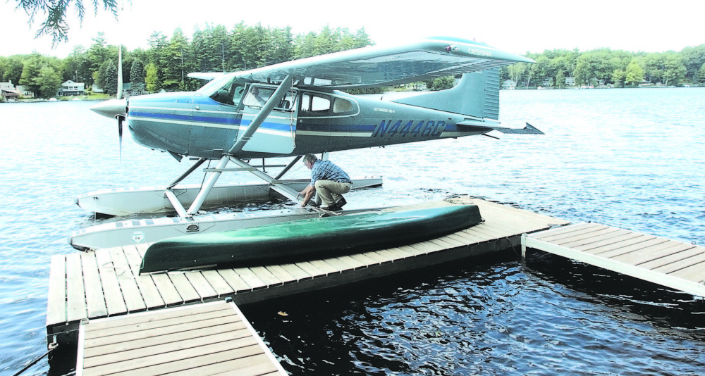 Bill McKay of Oakland secures his float plane to his dock on Messalonskee Lake in this August 2006 file photo after taking a short flight.