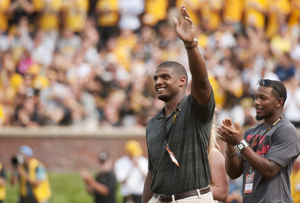 Former Missouri player Michael Sam, left, waves to fans has he and former teammate E.J. Gaines, right, are introduced during the first quarter of the South Dakota State-Missouri NCAA college football game Saturday, in Columbia, Mo.