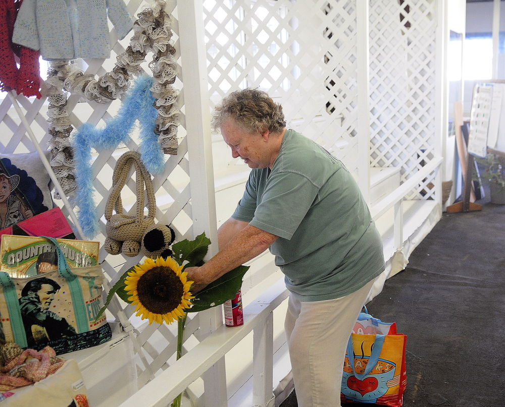 Marilyn Stinson of Richmond secures a sunflower Wednesday in the booth for the Richmond Grange in the exhibition hall at the Litchfield Fair. The annual agricultural exhibition begins Friday and wraps up Sunday.