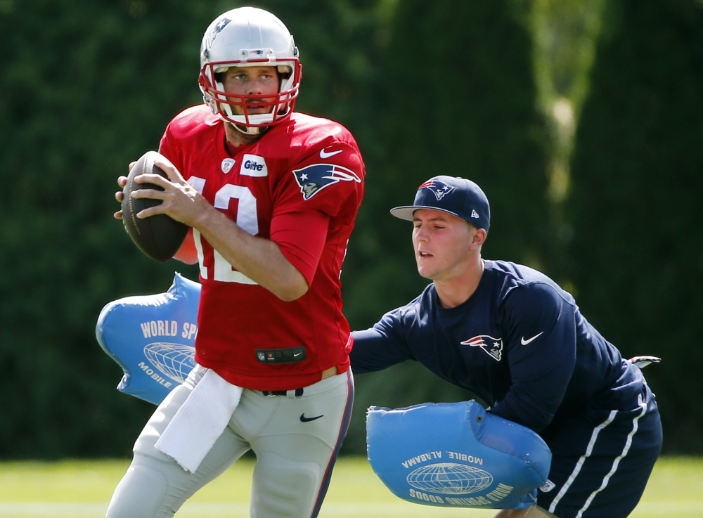 New England Patriots quarterback Tom Brady passes under pressure during a drill at practice Wednesday in Foxborough, Mass. The Patriots are preparing for their opening NFL football game against the Miami Dolphins on Sunday in Miami.
