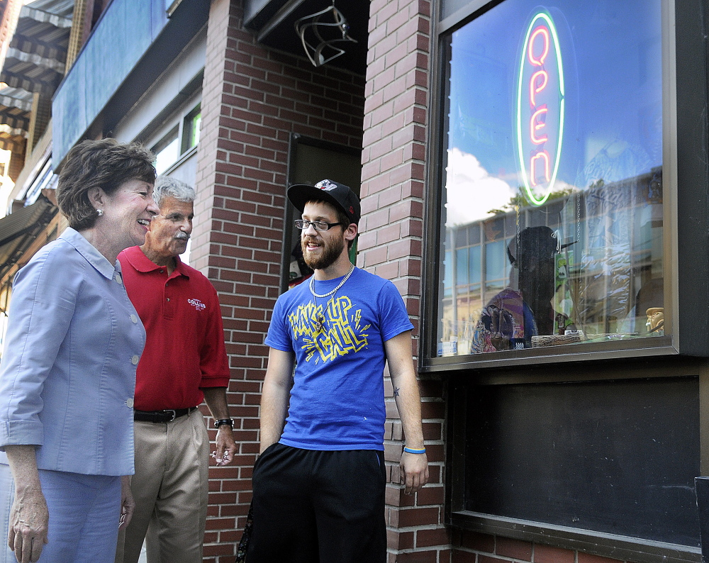 U.S. Sen. Susan Collins and State Sen. Roger Katz, R-Augusta, speak with Ralph Arbour on Wednesday outside Cosmic Charlie's in Augusta, where Arbour works. Katz accompanied Collins on a campaign swing through the downtown.