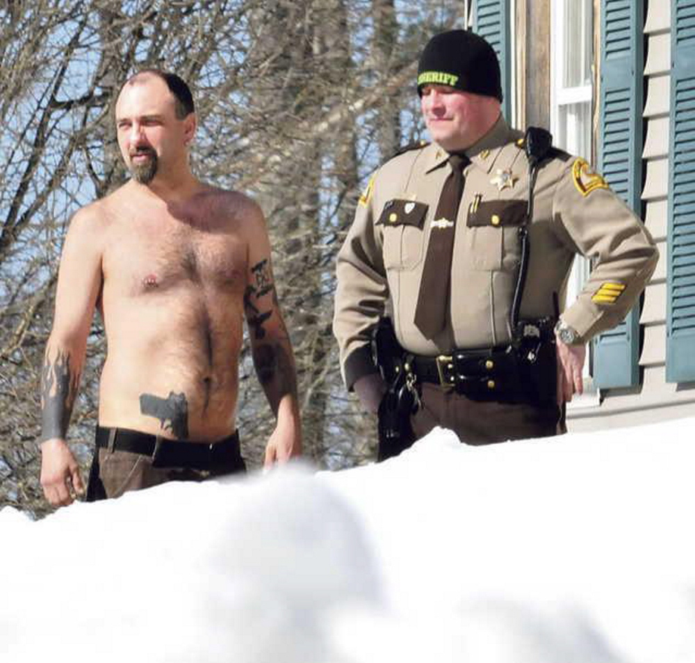 Norridgewock resident Michael Smith stands beside a Somerset County Sheriff deputy after he was coaxed out of his home by police on March 18. The tattoo of a pistol on his stomach was mistaken for a real firearm earlier, resulting in a call to police. No charges were filed.