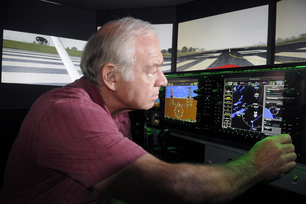University of Maine at Augusta aviation program coordinator Greg Jolda adjusts instruments on the school's new flight simulator Thursday at the Augusta campus.