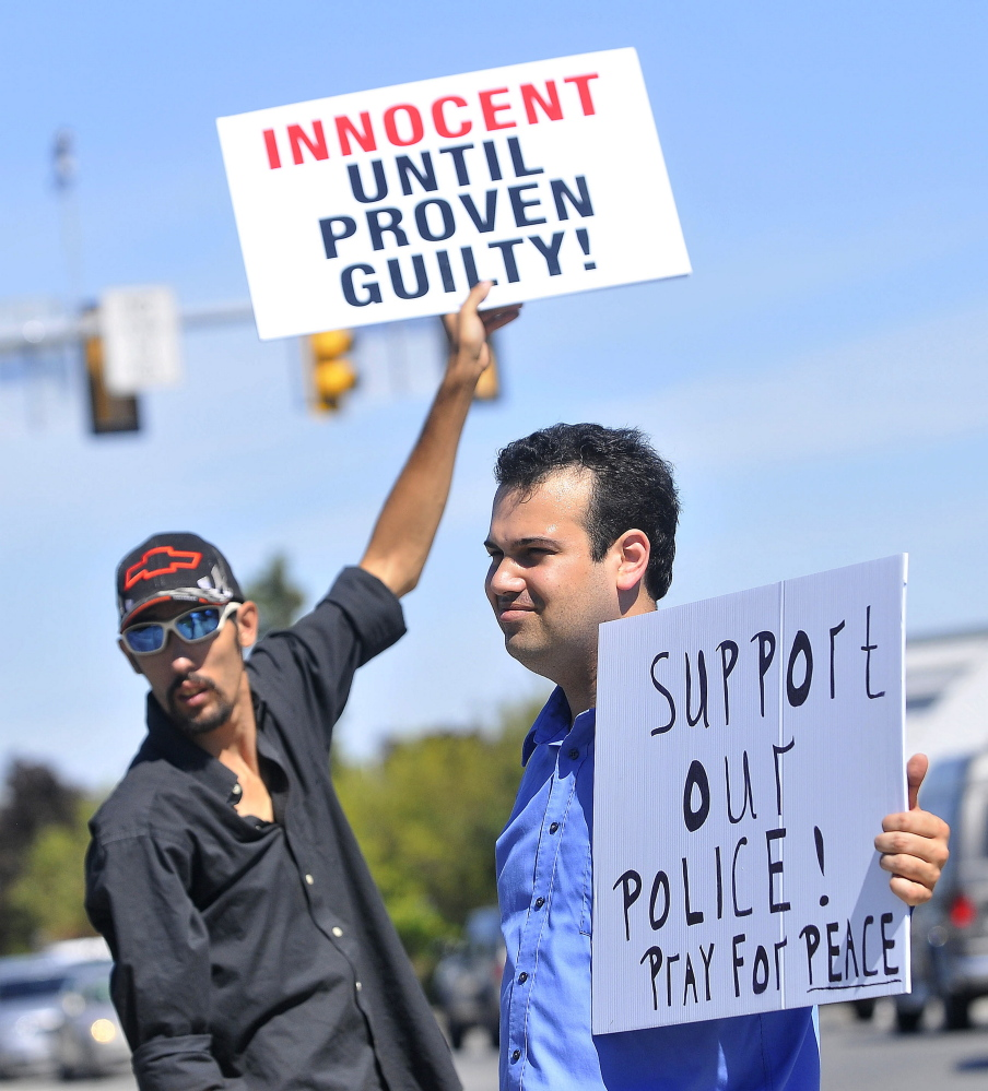 Jibryne Karter III, right, and Christopher Gruhn, back left, hold up signs Thursday on the corner of Main and Elm streets in Waterville in support of Officer Darren Wilson, who shot and killed Michael Brown last month in Ferguson, Mo.