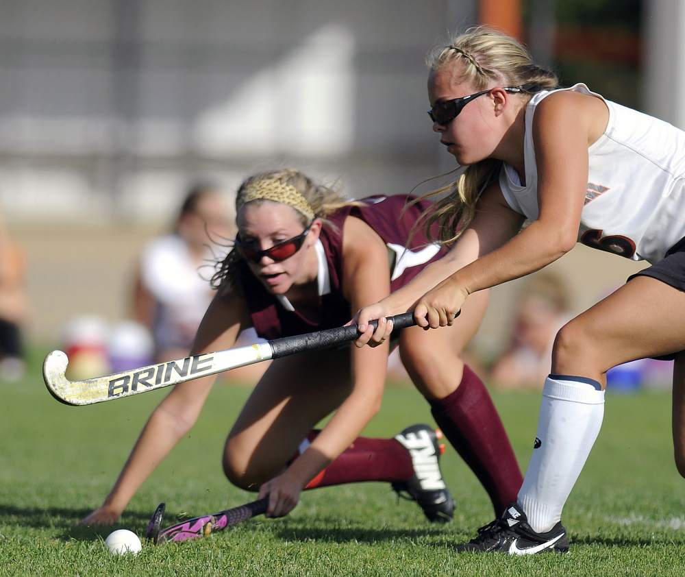 GARDINER, ME - SEPTEMBER: Gardiner Area High School's Emily Malinowski, right, drives Thursday September 4, 2014 past Nokomis High School's Shannon Kasprzak during a field hockey match up in Gardiner. (Photo by Andy Molloy/Staff Photographer)