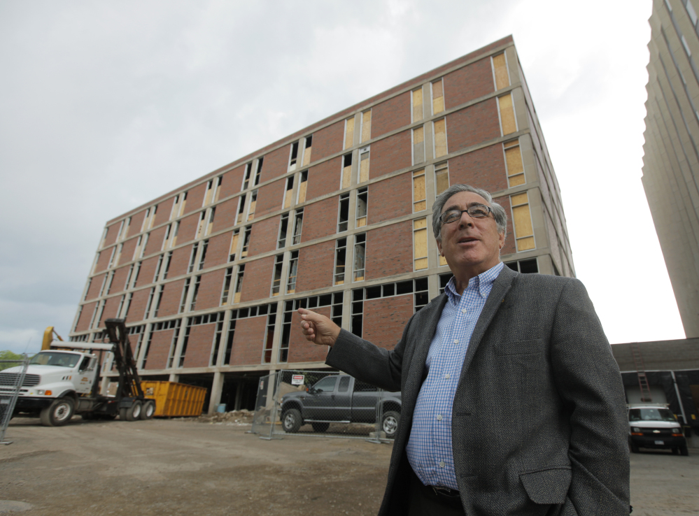 In this June 24, 2010 photo, developer Larry Glazer gestures toward a building to be demolished on Alexander Street in Rochester, N.Y.
