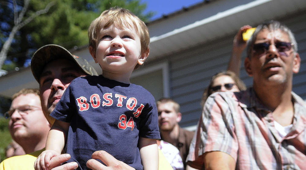 Zackary Hafner, 1, in the arms of his father, Miles, watches the demolition derby held at the Litchfield Fair on Sunday.