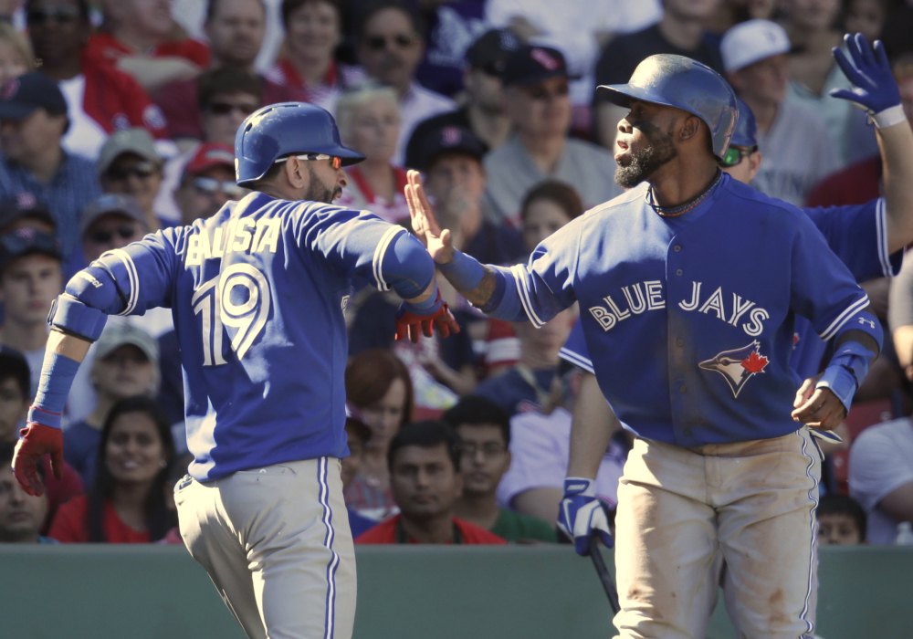 Toronto's Jose Bautista, left, is welcomed at home by Jose Reyes, right, after hitting a three-run home run off a pitch by Boston's Rubby De La Rosa in the fifth inning Sunday at Boston.