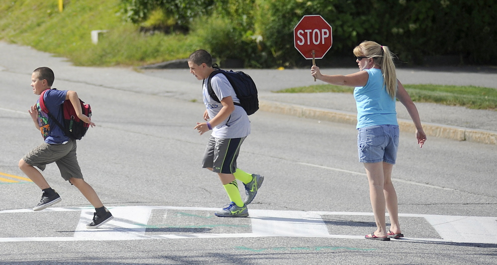 Former crossing guard Sherry McArthur escorts children across Western Avenue in Augusta during the first week of school. McArthur has volunteered to help cross this school year. The city eliminated paid crossing guards over the summer.