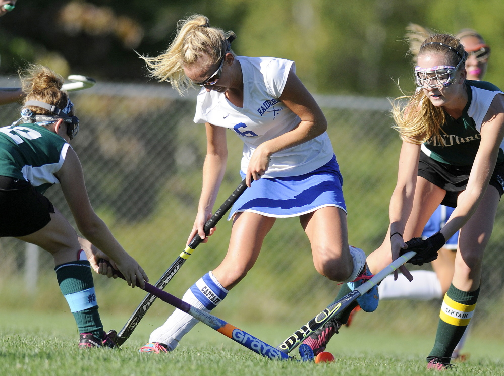 Oak Hill High School's Haylee Marshall, center, leaps over the sticks of Winthrop High School's Olivia Audet, right, and Kat Hayduke during a game Monday in Wales.