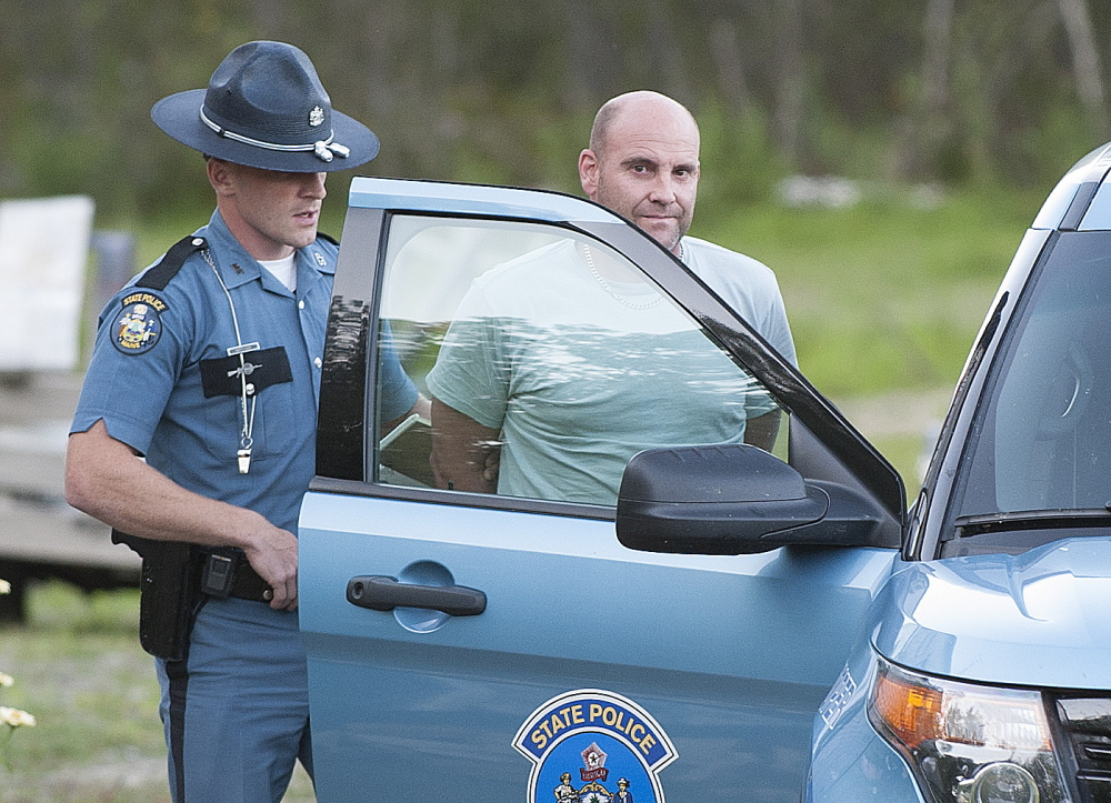 Maine State Police Trooper Scott Duff leads Marc Alberi of Newport to his cruiser in handcuffs after serving him with a search warrant on Monday.