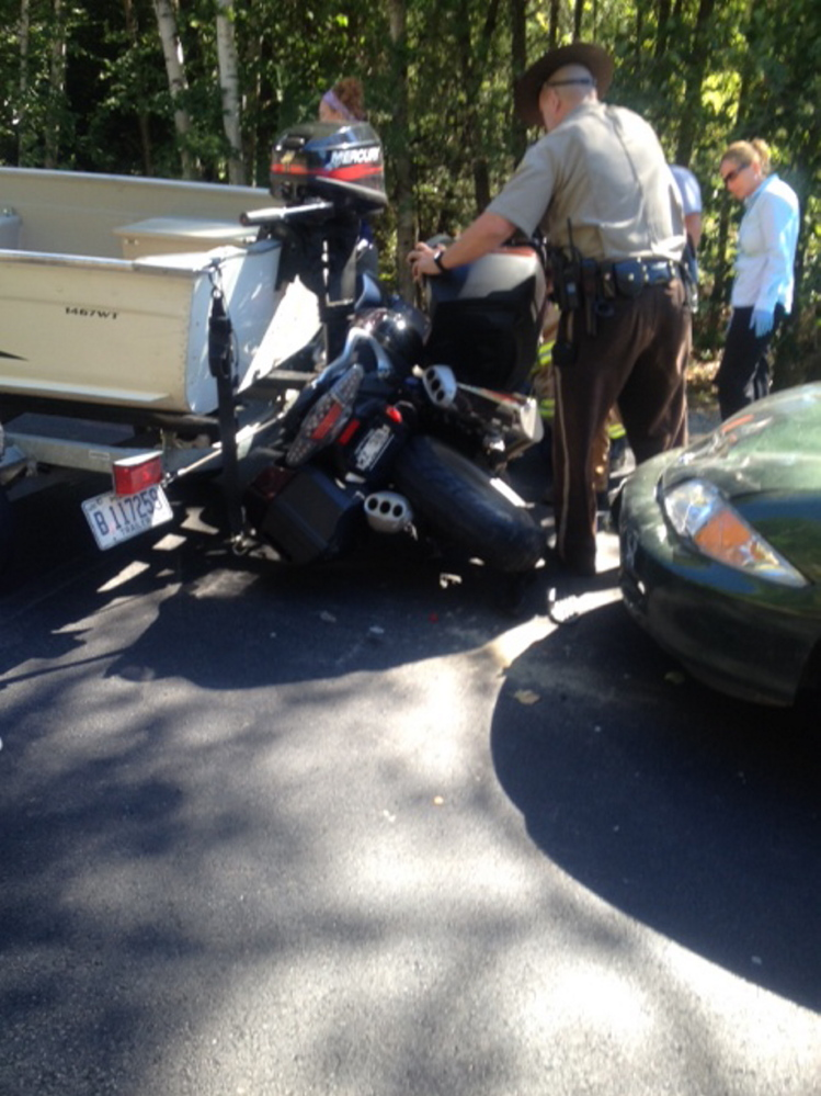 A deputy sheriff examines the wreckage after a motorcycle was sandwiched between a sedan and a boat being towed by a pickup truck Tuesday afternoon on U.S. Route 2 in Canaan. Three people were taken for hospital treatment, with the motorcycle driver being the most seriously injured.