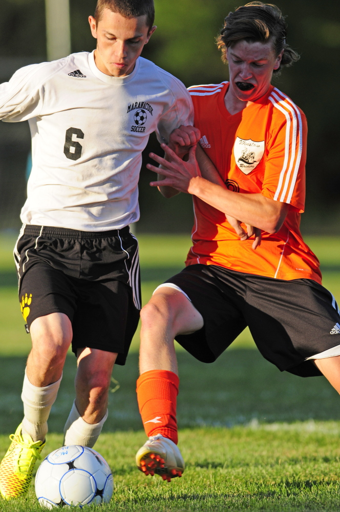 Winslow defender Ben Smith, right, kicks the ball away from Maranacook striker Kodey Solmitz Tuesday at the Ricky Gibson Field of Dreams in Readfield.