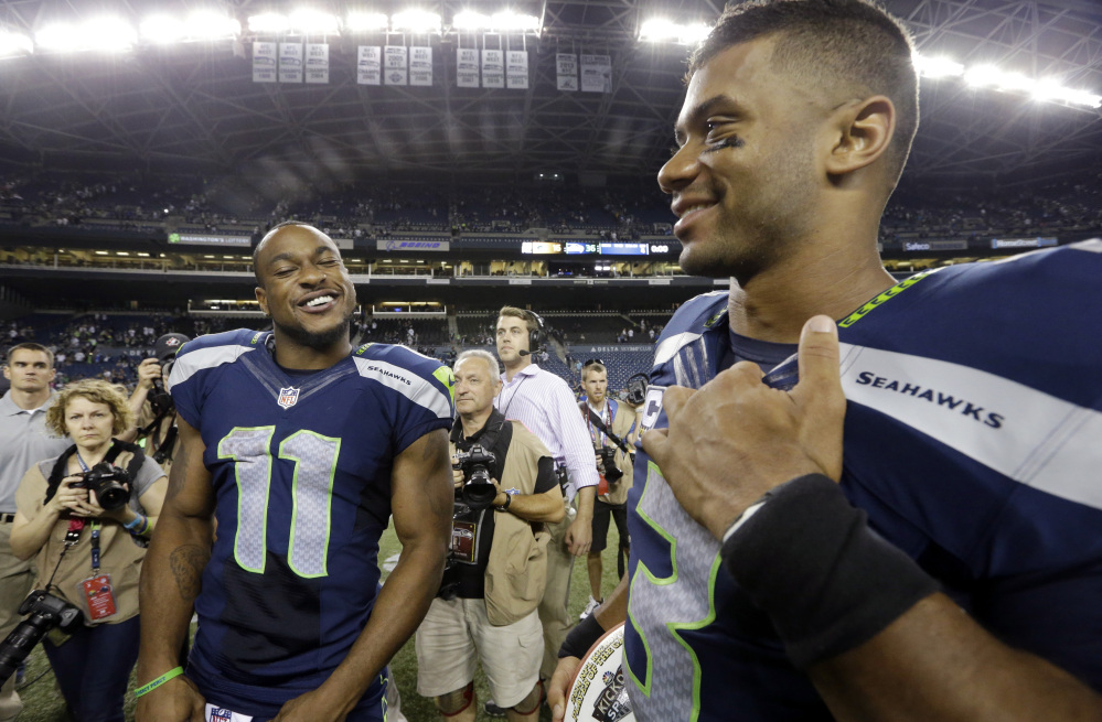 Seattle Seahawks' Percy Harvin (11) and Russell Wilson smile after the team defeated the Green Bay Packers 36-16 in an NFL football game, Sept. 4, in Seattle.