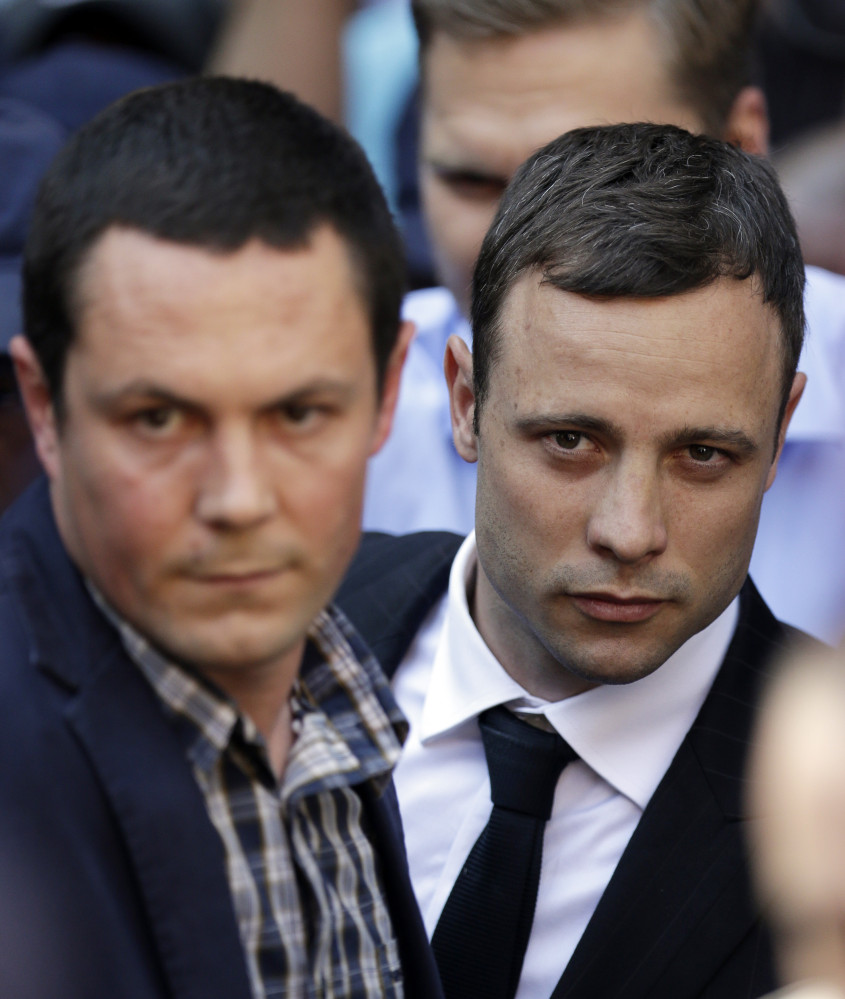 Oscar Pistorius, right, accompanied by a relative, leaves the high court in Pretoria Thursday.
